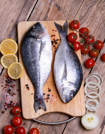 gilthead bream: Two fresh gilt-head bream fish on cutting board with lemon,onion and cherry tomato. Vertical.