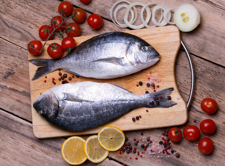 gilthead bream: Two fresh gilt-head bream fish on cutting board with lemon, onion and tomato. Horizontal.