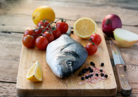 fresh gilt-head bream fish on cutting board with lemon, onion and tomato photo