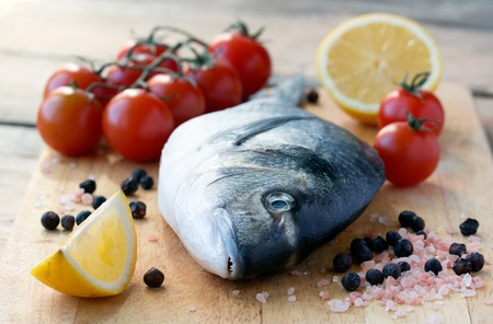 gilthead bream: fresh gilt-head bream fish on cutting board with lemon and tomato Stock Photo
