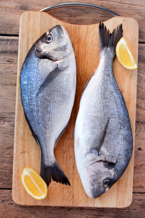 gilthead bream: Two fresh gilt-head bream fish with slices of lemon on cutting board on wooden  Stock Photo