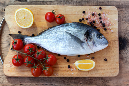 gilthead bream: Two fresh gilt-head bream fish with lemon, cherry tomato, pink salt and pepper on cutting board