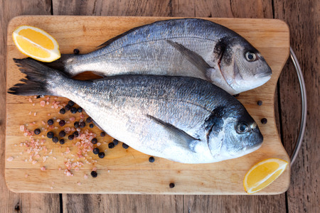 gilthead bream: Two fresh gilt-head bream fish with lemon, pink salt and pepper on cutting board