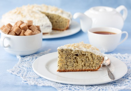 Delicious poppy seed Viennese cake with cup of tea, white tea pot and brown cane sugar on table close-up