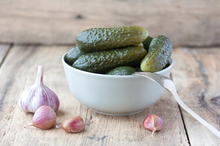 pickled cucumbers in white porcelain bowl  with fresh garlic on old wooden background photo