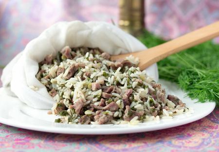 jewish cuisine: Uzbek traditional dish green pilaf in bag on white plate. Classic central asian Bukharian jewish cuisine.