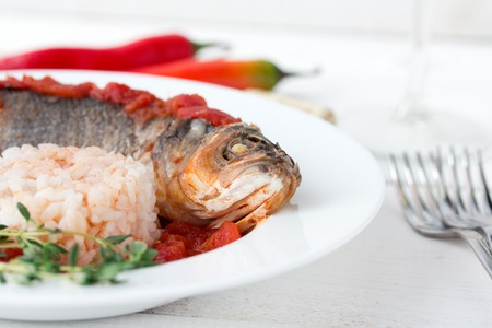 Steamed sea bass in tomato sauce with chili pepper on white table. photo