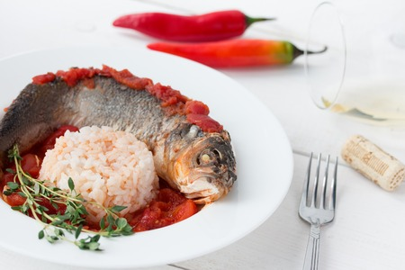 Steamed sea bass in tomato sauce with chili pepper and glass of white wine on white table. photo