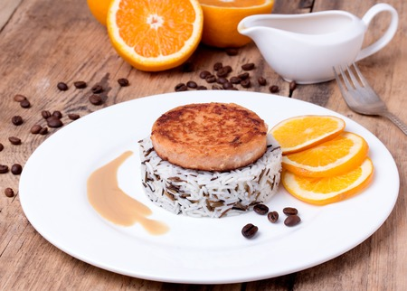 Salmon medallion with mixed cooked rice on white plate with coffee beans and orange. Wooden background photo