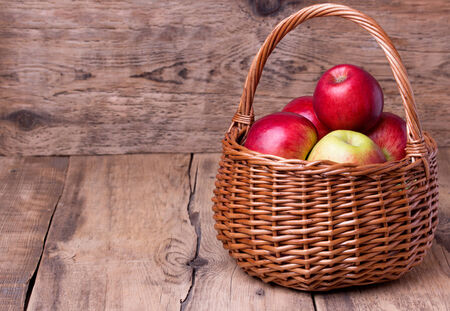 jewish home: Fresh red apples in wicker basket over wooden background. Copyspace. Stock Photo