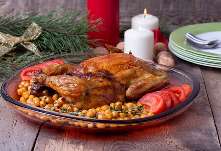 Roasted Christmas whole chicken with chickpeas and tomato on wooden table. Candle, walnut and pine branches at background. photo