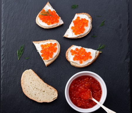 Bread with fresh cream cheese and red caviar on black slate plate photo