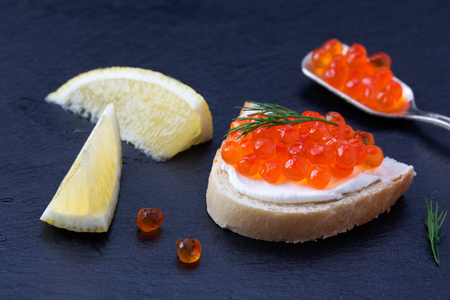 Bread with fresh cream cheese, red caviar and lemon on black slate plate photo