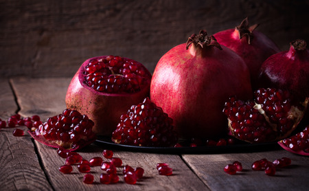 a pomegranate: Some red juicy pomegranate on dark rustic wooden table
