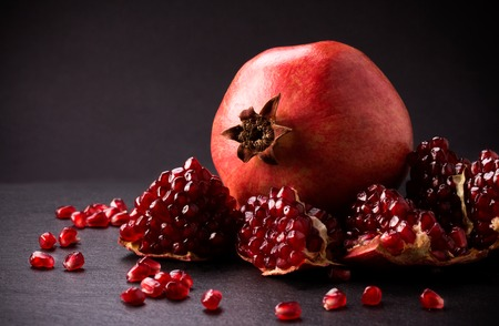 Some red juicy pomegranate, whole and broken, on black slate plate Stock Photo