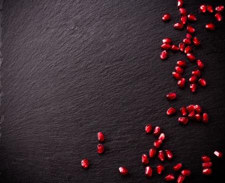 Ripe pomegranate seeds on rough black slate background. Copy space.
