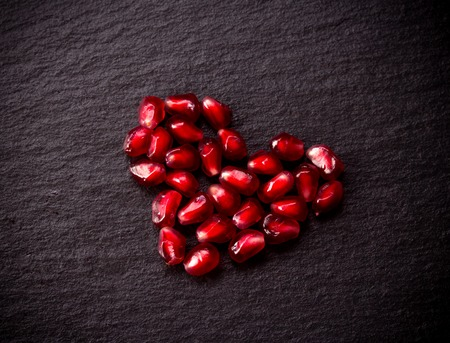 Ripe pomegranate seeds in form of heart on black rough slate background.