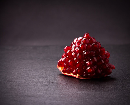 a pomegranate: Some red juicy pomegranate, whole and broken, on black slate plate Stock Photo