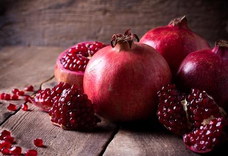 어두운 소박한 나무 테이블에 일부 육즙이 붉은 석류, 전체 및 깨진,