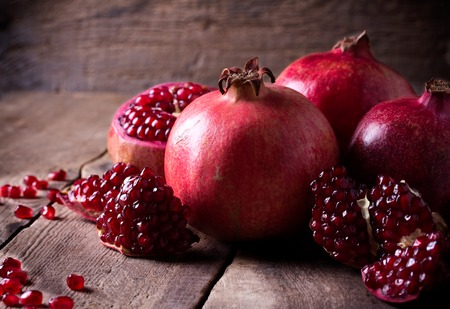 a pomegranate: Some red juicy pomegranate, whole and broken, on dark rustic wooden table