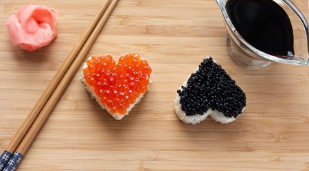 sushi chopsticks: Two heart shaped sushi with salmon roe and beluga caviar on wooden desk. ginger, chopsticks and soy sauce.