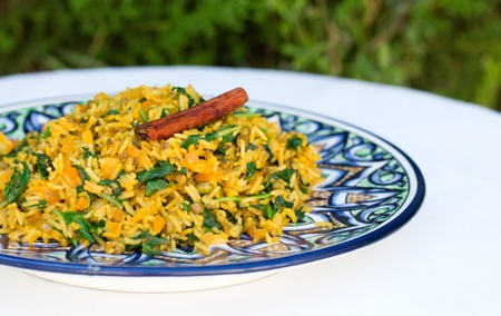 traditional Indian dish called khichdi. Included rice, mung bean, cumin and curry with cinnamon stick on plate with asian ornament 版權商用圖片