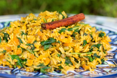 indian bean: traditional Indian dish called khichdi. Included rice, mung bean, cumin and curry with cinnamon stick on plate with asian ornament Stock Photo
