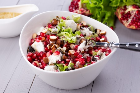 Healthy salad with pomegranate seeds, almond, feta cheese and black rice in white bowl.