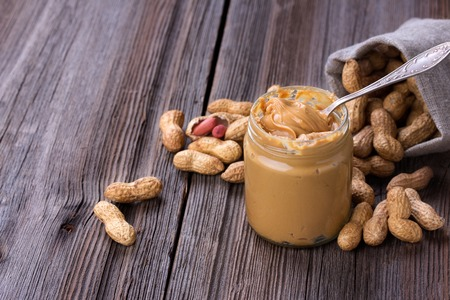 Fresh made creamy Peanut Butter in a glass jar and peanuts on old wooden table. Copy space 스톡 콘텐츠