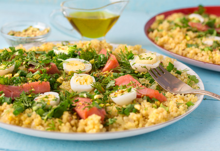 Tasty breakfast dish kedgeree, made with hot smoked salmon, egg, rice, curry powder and parsley. Traditional british dish.