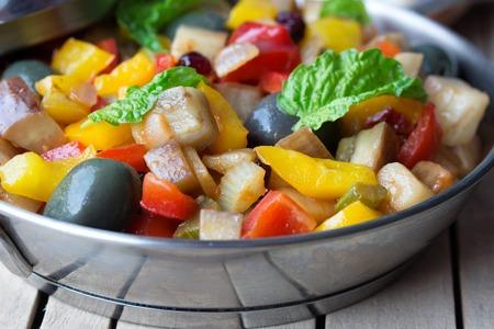 steel pan: Caponata, ensalada de verdura cocida hecha de berenjena frita picada. Plato siciliano tradicional. Se sirve en un plato de acero inoxidable en una mesa de madera envejecida.
