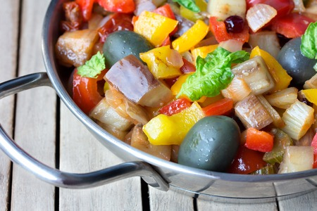 steel pan: Caponata, cooked vegetable salad made from chopped fried eggplant. Traditional sicilian dish. Served in a stainless steel pan on an aged wooden table.