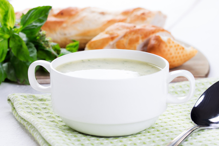 Vegetable cream soup in white bowl with baguette Stock fotó