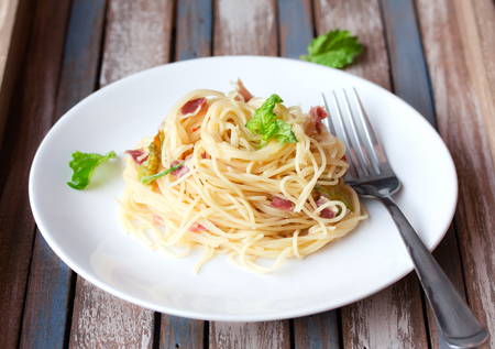 Italian pasta with cheese, prosciutto and basil on vintage rustic wooden background Stock fotó