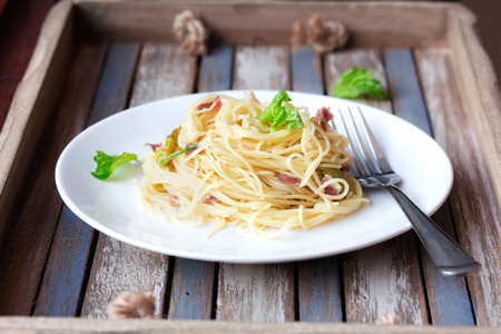spaghetti dinner: Italian pasta with cheese, prosciutto and basil on vintage rustic wooden background Stock Photo