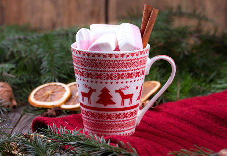 Mug of hot chocolate with marshmallows and cinnamon sticks. Christmas or new year still life. Mug is decorated with scandinavian christmas ornaments.