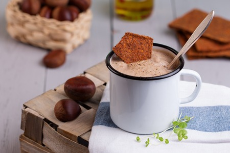 Creamy chestnut soup in white enamel mug with roasted chestnuts  on grey painted wooden textural background Stock fotó