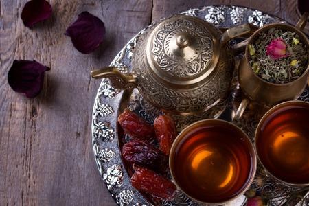 Traditionele Arabische theeset en gedroogde dadels. Oude houten achtergrond