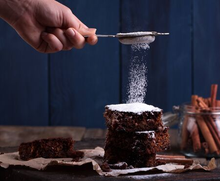 dundee: Powder of sugar is hung on a Pieces of Christmas chocolate cake on wooden background.