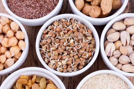 seeds of various: Bowls of various legumes and seeds. Lentils, sesame seeds, pistachio nuts, flaxseed, raisins, peanuts and chickpeas.   Sprouted legumes. Wooden background
