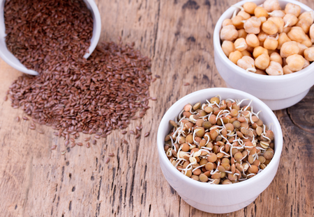 seeds of various: Bowls of various legumes and seeds. Flaxseed, peanuts and chickpeas.  Sprouted legumes. Wooden background