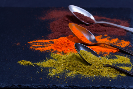 herbs de provence: Colorful spices in spoons. Saffron, curcuma on black background. Stock Photo
