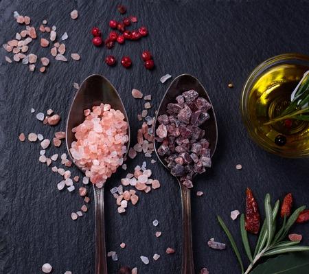 himalayan salt: Black salt and Pink Himalayan salt in spoons. Various spices on black slate desk. Stock Photo