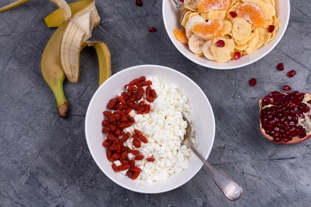kinfolk: Healthy breakfast - corn flakes, goji berry, cottage cheese, milk and fruit. Top view Stock Photo