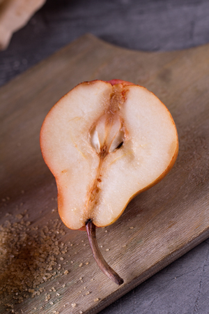 anjou: Sliced red anjou pears on a rustic wooden cutting board with brown sugar