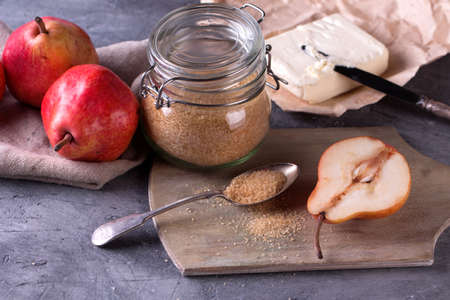 anjou: Healthy breakfast. Sliced red anjou pears on a rustic wooden cutting board with brown sugar Stock Photo