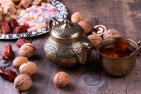 sugar palm: Traditional arabic tea set, walnut and dried dates. Oriental sweet on silver plate. Turkish delight, halva, dates and others on old wooden background