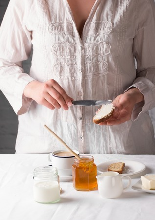 rusk: Healthy eating. Young girl preparing healthy breakfast with honey, yogurt and buttered rusk