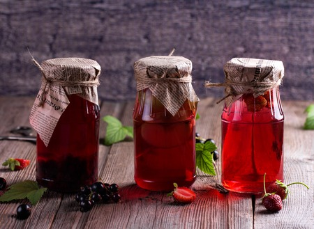 colored bottle: Canned homemade apple and berry compotes in glass jars. Old wooden desk. Rustic. Vintage. Stock Photo