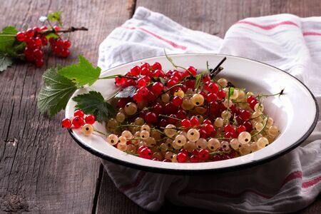 red and white currant in enamel dish on wooden background. Dark photo.